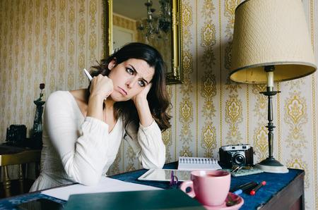 Mujer joven cansada y abrumada estudiando o trabajando en casa. Mujer empresaria aburrido o estudiante. La frustración y el estrés profesional. Foto de archivo - 41070062