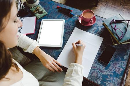 correo electronico: Trabajar en concepto de hogar. Empresario escrito mujer de negocios y tomar notas usando su tableta digital en el escritorio retro completos objetcs og. Foto de archivo