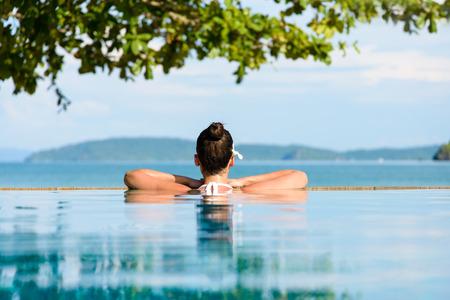 relajado: Rel�jese y concepto de spa. Mujer con una flor en el pelo se relaja en una piscina en Krabi, Tailandia.