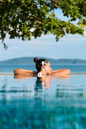 휴식과 스파 개념. 크라비, 태국에서 수영장에서 휴식 머리에 꽃을 가진 여자입니다.