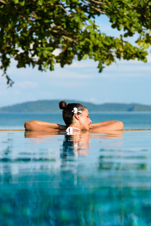Relax and spa concept. Woman with a flower in hair relaxing in a pool at Krabi, Thailand.