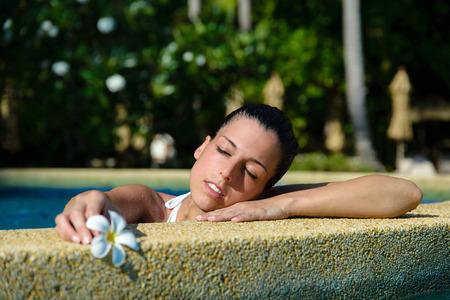 美しい女性を楽しむリゾート スパ プールでおくつろぎください。美容と身体のケア概念。