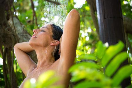 Entspannte glückliche Frau, die Spa-Dusche im Freien in exotischen Garten.
