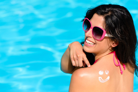 sunscreen: Happy woman pointing sunscreen lotion funny smiley on her back and enjoying summer vacation at swimming pool. Beautiful brunette sunbathing. Skin care and sun protection concept. Stock Photo