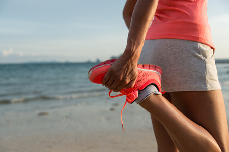Running and healthy lifestyle concept. Runner footwear close up. Woman warming up for training at the beach.