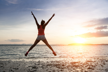 beack: Sporty woman jumping and enjoying freedom and success towards the sun and sea on sunset at the beach. Stock Photo