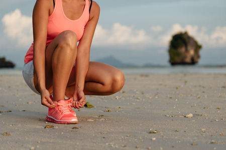 Woman lacing sport shoes and getting ready for running and exercising at beach on summer, Krabi, Thailand. Fitness woman training outdoor.