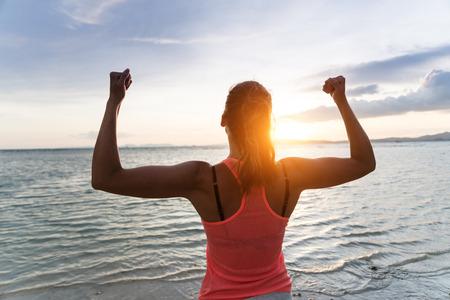 Erfolg: Sporty starke Frau Heben der Arme und Freiheit und Erfolg genießen in Richtung der Sonne und Meer auf Sonnenuntergang am Strand. Erfolgreiche Sportlerin gegen die Sonne.
