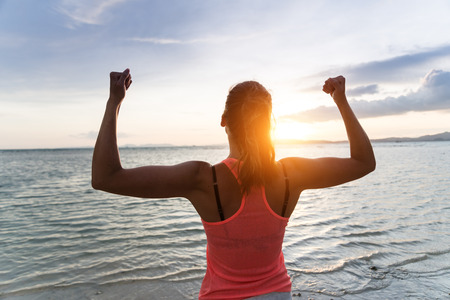 achieve goal: Sporty strong woman raising arms and enjoying freedom and success towards the sun and sea on sunset at the beach. Successful female athlete against the sun.