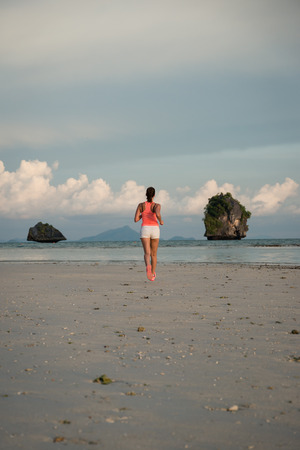 back  view: Back view of woman running at beach on summer. Female athlete training and exercising outdoor.