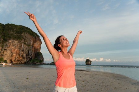 Motivated sporty woman celebrating workout success at the beach, Krabi, Thailand. Female athlete raising arms and enjoying freedom. Stock Photo