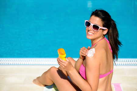 skin protection: Woman applying sunscreen or suntan lotion in her shoulder for solar skin protection at swimming pool. Brunette girl enjoying summer vacation.