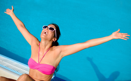 outstretching: Blissful woman having fun at swimming pool on summer vacation. Successful happy girl with sunglasses raising arms at poolside.