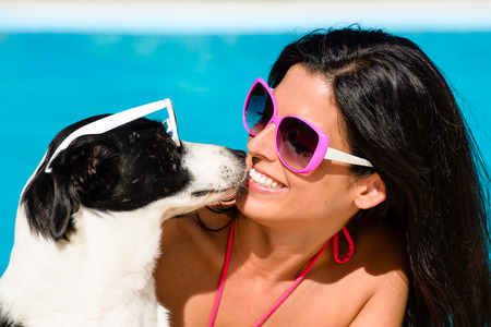 Happy woman and cute dog wearing sunglasses and having fun on summer vacation at swimming pool.