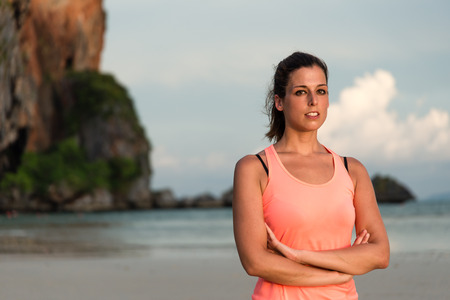 motivated: Fitness woman portrait. Motivated female athlete with arms crossed at the beach, Krabi, Thailand.