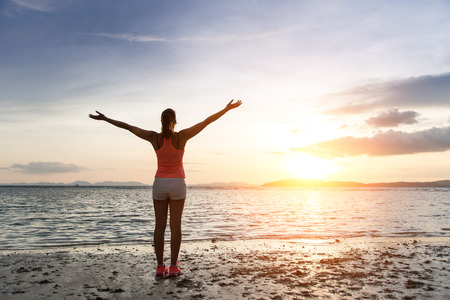 Sporty woman enjoying relax and freedom towards the sun and sea on sunset at the beach. Tranquility and bliss concept.