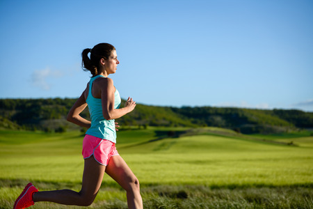 Sporty woman running. Female athlete training outdoor against countryside green field.