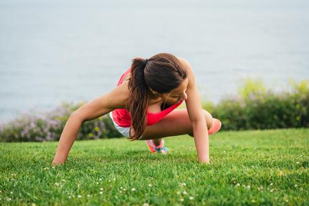 Fitness woman training core outside. Female athlete exercising on summer or spring. Reklamní fotografie