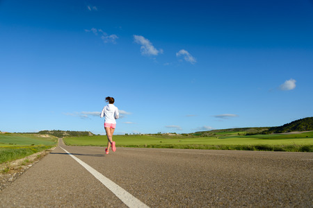 country road: Sporty woman running on country side road back view. Female athlete training outdoor.