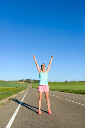 achiever: Happy woman celebrating running and sport success. Female athlete raising arms to the sky during training on countryside road. Stock Photo