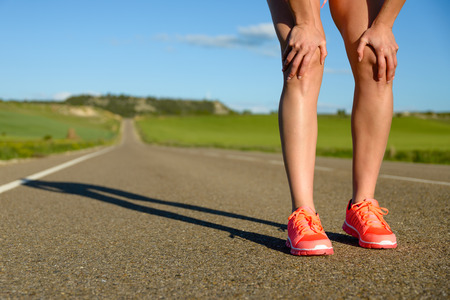 fitness motivation: Running challenge concept. Runner legs and sport shoes on asphalt countryside road ready for training.