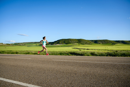 side of the road: Sporty woman running on country side road. Female athlete training and exercising outdoor. Stock Photo