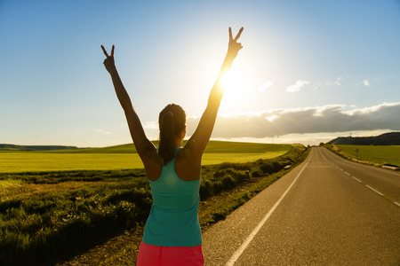 victory: Woman celebrating running and training success on countryside road during sunset or sunrise. Female runner raising arms towards the sun.