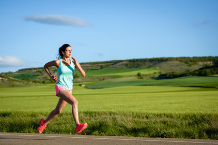 country side: Sporty woman running fast on country side road. Female athlete training outdoor.