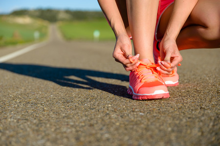 Running challenge concept. Female athlete tying sport footwear laces on road before training. Archivio Fotografico