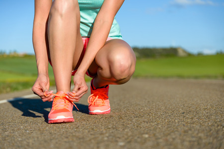 lacing: Running and sport concept. Female athlete tying sport footwear laces on road before training. Stock Photo