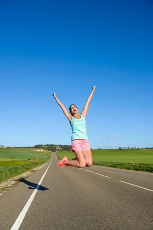 arm: Happy woman jumping for celebrating running and sport success. Female athlete raising arms to the sky during training on countryside road.