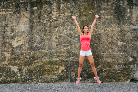 Happy female athlete jumping for celebrating exercising and fitness success.