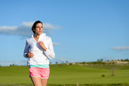 woman in field: Sporty woman running and training at countryside field. Motivated female runner exercising. Stock Photo