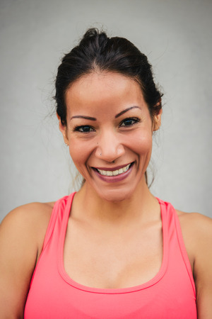 brunette woman: Happy female athlete close up portrait. Sporty woman smiling and looking at camera. Stock Photo