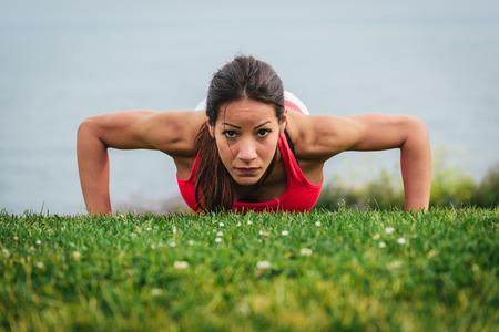push ups: Fitness woman doing push ups and exercising outdoor on summer. Motivated female athlete training hard.