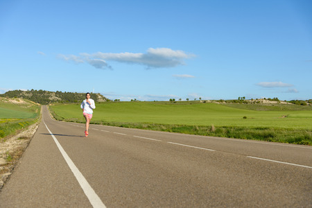 side road: Sporty woman running on country side road. Female athlete training outdoor. Stock Photo
