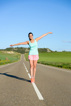 equilibrium: Playful sporty woman exercising equilibrium and balance on countryside road lines. Female runner outdoor.