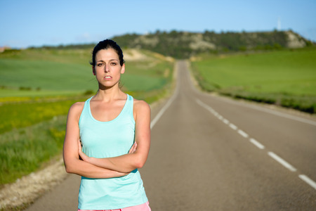 motivated: Sporty motivated woman portrait. Female athlete crossing arms after running and exercising on countryside road.