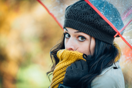 shivering: Sad woman shivering and suffering cold autumn wind and rain. Brunette female covering her mouth with warm scarf because of fall season bad weather.