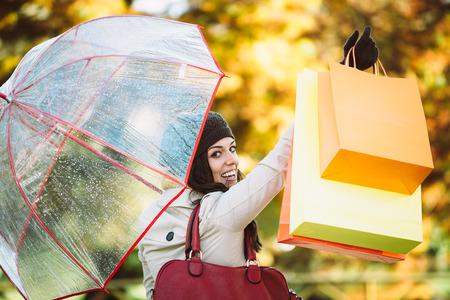 blissful: Blissful woman holding shopping bags and having fun buying in autumn rain. Successful female shopper outside in fall season.