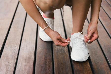 Frau Schnürung Fitness- und Sportschuhe für den gesunden Lifestyle-Konzept. Weibliche Athleten immer bereit für Training Training und Herausforderung.