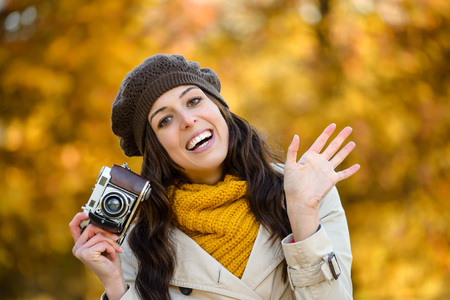 fashionable woman: Happy woman waving and taking photos with retro camera againts autumn park background. Fashionable girl wearing fall season warm clothes. Stock Photo