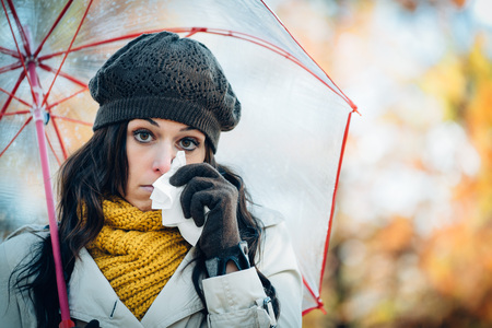 umbrella month: Sad woman with cold or flu blowing her nose with a tissue under autumn rain. Brunette female sneezing and wearing warm clothes against cold weather. Illness, depression and allergy concept. Stock Photo