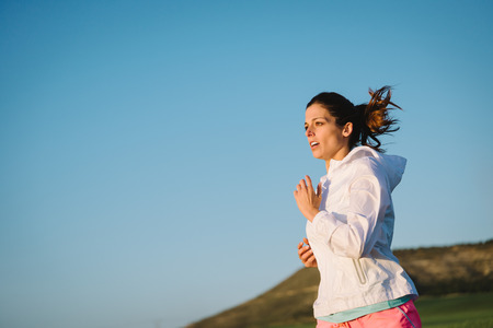 Motivated woman running against clear blue sky background for copy space. Female athlete training outdoor at countryside. photo