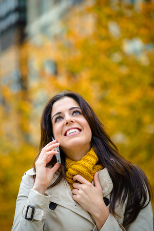 blissful: Happiness in the city in autumn. Blissful woman on smartphone call waking on the street wearing scarf and raincoat.