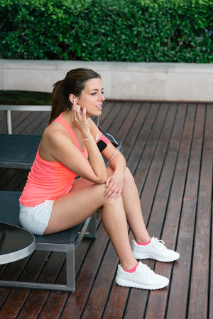 motivated: Motivated sporty woman relaxing before  outdoor fitness workout. Female athlete taking a training break for resting.