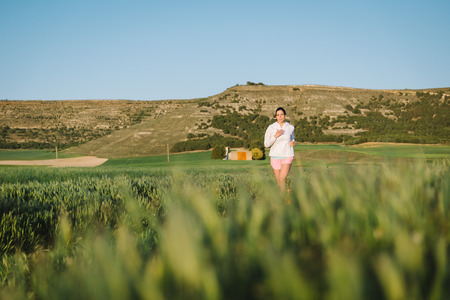 Sporty woman running on country road surrounded by field. Athlete training and exercising outdoor at sunset or morning. photo