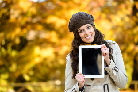 touchpad: Woman holding blank screen digital tablet in autumn outdoor. Young female holding touchpad for copy space message or information.