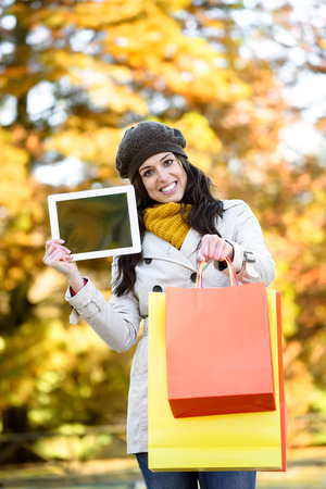 mujer alegre: Fashion woman showing digital tablet blank screen card and carrying shopping bags after buying in autumn. Foto de archivo