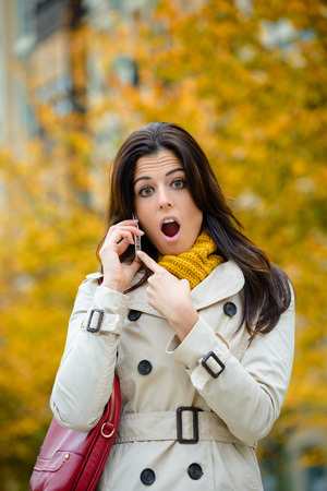awe: Surprised woman on phone call outdoor on the street in autumn. Urban female pointing her smartphone with mouth open or jaw dropping. Stock Photo